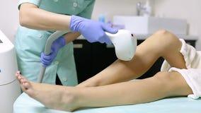Το Cosmetologist κάνει την αφαίρεση τρίχας λέιζερ στα πόδια του ασθενή Διαδικασία Epilation φιλμ μικρού μήκους