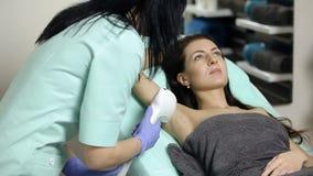 Το Cosmetologist κάνει την αφαίρεση τρίχας λέιζερ των μασχαλών του ασθενή Διαδικασία Epilation φιλμ μικρού μήκους