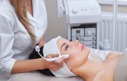 Το cosmetologist κάνει την επεξεργασία διαδικασίας Couperose του του προσώπου δέρματος μιας όμορφης, νέας γυναίκας στοκ φωτογραφία
