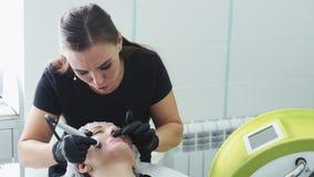 Το Cosmetologist κάνει την υδρο διαδικασία ξεφλουδίσματος και καθαρισμού στο υπομονετικό πρόσωπο Αποφλοίωση του του προσώπου δέρμ απόθεμα βίντεο