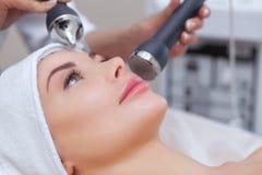 Το cosmetologist κάνει τη διαδικασία έναν υπερηχητικό καθαρισμό του του προσώπου δέρματος μιας όμορφης, νέας γυναίκας σε ένα σαλό στοκ φωτογραφία με δικαίωμα ελεύθερης χρήσης