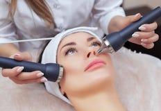 Το cosmetologist κάνει τη διαδικασία έναν υπερηχητικό καθαρισμό του του προσώπου δέρματος μιας όμορφης, νέας γυναίκας σε ένα σαλό στοκ φωτογραφία