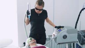 Το Cosmetologist κάνει τη διαδικασία αποφλοίωσης προσώπου άνθρακα στη νέα γυναίκα στα προστατευτικά γυαλιά, σε αργή κίνηση απόθεμα βίντεο