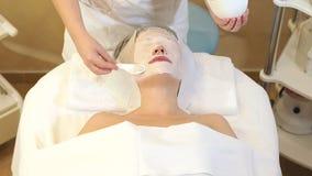 Το cosmetologist κινηματογραφήσεων σε πρώτο πλάνο εφαρμόζει μια παχιά μπεζ μάσκα στο πρόσωπο και τα μάτια της γυναίκας απόθεμα βίντεο