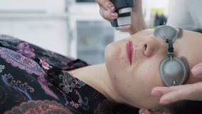 Το cosmetologist κινηματογραφήσεων σε πρώτο πλάνο κάνει την επεξεργασία λέιζερ στο νέο πρόσωπο γυναικών, αφαίρεση της ακμής, σε α φιλμ μικρού μήκους