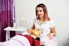Το Cosmetologist κοιτάζει στη κάμερα δίνοντας μια του προσώπου επεξεργασία με μια χρυσή μάσκα σε έναν πελάτη ενός σαλονιού ομορφι Στοκ φωτογραφίες με δικαίωμα ελεύθερης χρήσης