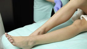 Το Cosmetologist σκουπίζει τα υπομονετικά πόδια ` s με το σφουγγάρι βαμβακιού πριν από τη διαδικασία απολύμανση φιλμ μικρού μήκους