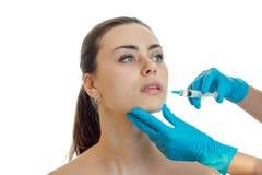 Το Cosmetologist στα γάντια κάνει εισάγει το εμβόλιο στο πρόσωπο μιας νέας όμορφης κινηματογράφησης σε πρώτο πλάνο κοριτσιών Στοκ Εικόνα