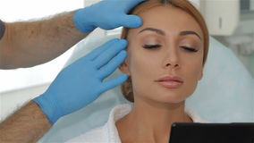 Το Cosmetologist τεντώνει το δέρμα πέρα από το brow του πελάτη απόθεμα βίντεο