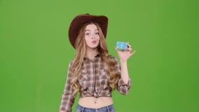 Το Cowgirl σε ένα καπέλο παρουσιάζει δάχτυλό της στην κάρτα, διαφημίζει τα αγαθά πράσινη οθόνη απόθεμα βίντεο
