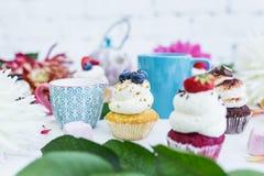 Το Cupcakes με τα φρέσκα μούρα ανθίζει και φεύγει, ένα φλυτζάνι του τσαγιού ή καφές και μια κατσαρόλα Στοκ Εικόνα