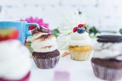 Το Cupcakes με τα φρέσκα μούρα ανθίζει και φεύγει, ένα φλυτζάνι του τσαγιού ή καφές Στοκ φωτογραφία με δικαίωμα ελεύθερης χρήσης
