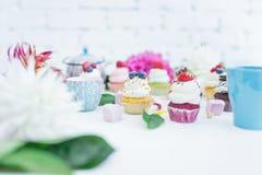 Το Cupcakes με τα φρέσκα μούρα ανθίζει και φεύγει, ένα φλυτζάνι του τσαγιού ή καφές Στοκ Εικόνες