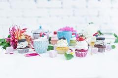 Το Cupcakes με τα φρέσκα μούρα ανθίζει και φεύγει, ένα φλυτζάνι του τσαγιού ή καφές και μια κατσαρόλα Στοκ Εικόνες