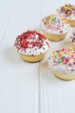Το Cupcakes με την άσπρη κρέμα και ψεκάζει στο άσπρο υπόβαθρο Στοκ Εικόνες