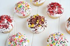 Το Cupcakes με την άσπρη κρέμα και ψεκάζει στο άσπρο υπόβαθρο Στοκ φωτογραφία με δικαίωμα ελεύθερης χρήσης