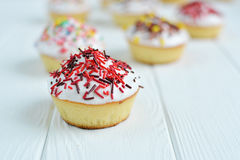 Το Cupcakes με την άσπρη κρέμα και ψεκάζει στο άσπρο υπόβαθρο Στοκ φωτογραφίες με δικαίωμα ελεύθερης χρήσης