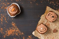 Το Cupcakes με την κρέμα σοκολάτας είναι διακοσμημένο σε ένα σκοτεινό αγροτικό υπόβαθρο Τοπ άποψη, διάστημα αντιγράφων Στοκ εικόνα με δικαίωμα ελεύθερης χρήσης