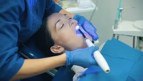 Το Dentis βάζει τις οδοντικές γαρνιτούρες με το μπλε φως απόθεμα βίντεο