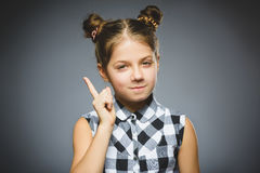 Το Displeased και το περιφρονητικό κορίτσι με απειλούν το δάχτυλο στο γκρίζο υπόβαθρο στοκ εικόνες