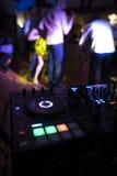 Το DJ αναμιγνύει τη διαδρομή στο νυχτερινό κέντρο διασκέδασης στο κόμμα με τους χορεύοντας ανθρώπους στο υπόβαθρο θαμπάδων Στοκ Εικόνα
