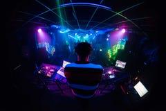 Το DJ αναμιγνύει τη μουσική σε ένα νυχτερινό κέντρο διασκέδασης με το χορό ανθρώπων στοκ φωτογραφίες με δικαίωμα ελεύθερης χρήσης