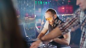 Το DJ παίζει τη μουσική σε ένα κόμμα σε ένα νυχτερινό κέντρο διασκέδασης απόθεμα βίντεο
