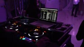 Το DJ στο disco εργάζεται πίσω από τον τηλεχειρισμό Πίστα χορού και ελαφριά μουσική απόθεμα βίντεο