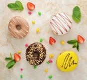 Το Donuts και η φράουλα, μέντα βγάζουν φύλλα στο μαρμάρινο υπόβαθρο Στοκ Εικόνες