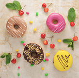 Το Donuts και το κεράσι, μέντα βγάζουν φύλλα στο μαρμάρινο υπόβαθρο Στοκ Εικόνες