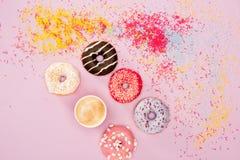Το Donuts με το διαφορετικό γλυκό λούστρο, ψεκάζει και φλιτζάνι του καφέ στο ροζ Υπόβαθρο σοκολάτας Donuts Στοκ Φωτογραφίες
