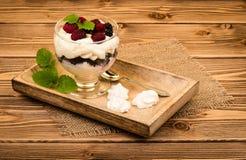 Το Eton βρωμίζει - παραδοσιακό αγγλικό επιδόρπιο με την κρέμα, τα μούρα και τις μαρέγκες στο ξύλινο υπόβαθρο Στοκ Φωτογραφία