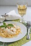 Το Fettuccine με το κοτόπουλο σε μια κρεμώδη σάλτσα εξυπηρέτησε με ένα ποτήρι του κρασιού Στοκ εικόνες με δικαίωμα ελεύθερης χρήσης