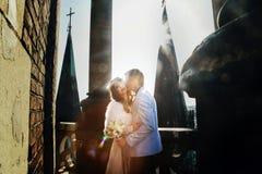 Το Fiance φιλά μια νύφη στο νεοσσό στις ακτίνες του φωτός του ήλιου στο μέτωπο Στοκ φωτογραφία με δικαίωμα ελεύθερης χρήσης
