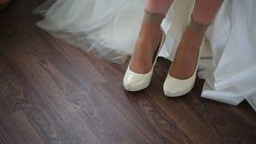 Το Fiancee βάζει στο ζευγάρι των άσπρων νυφικών παπουτσιών για την έξοδο φιλμ μικρού μήκους