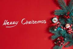 Το FIR διακλαδίζεται σύνορα στο κόκκινο υπόβαθρο, καλό για το σκηνικό Χριστουγέννων Η επιγραφή - Χαρούμενα Χριστούγεννα Στοκ φωτογραφία με δικαίωμα ελεύθερης χρήσης