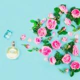 Το Flatlay του ψεκασμού του ρόδινου τσαγιού αυξήθηκε λουλούδια και πέταλα από το όμορφο μπουκάλι αρώματος στο μπλε υπόβαθρο Φρέσκ Στοκ Εικόνες