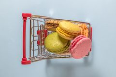 Το Flt βάζει του μικροσκοπικού συνόλου καροτσακιών αγορών των ζωηρόχρωμων μπισκότων macarons Στοκ Φωτογραφίες