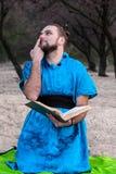 Το Fooling γύρω από το όμορφο γενειοφόρο άτομο στο μπλε κιμονό με το δάχτυλο στη συνεδρίαση μύτης και η εκμετάλλευση κρατούν στοκ φωτογραφίες με δικαίωμα ελεύθερης χρήσης