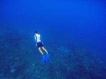 Το Freediver κολυμπά υποβρύχιο στη βαθιά μπλε θάλασσα Το άτομο κολύμβησης με αναπνευστήρα βουτά μέχρι την επιφάνεια νερού Στοκ Εικόνες