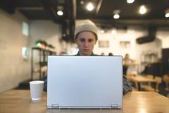 Το freelancer λειτουργεί για ένα lap-top σε έναν άνετο καφέ Ένας σπουδαστής χρησιμοποιεί ένα lap-top σε έναν καφέ Εστίαση στο lap Στοκ Εικόνες