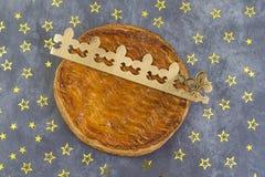 Το Galette des rois, γαλλικό kingcake με μια χρυσή κορώνα σε ένα γκρίζο υπόβαθρο πλακών διασκόρπισε με τα χρυσά αστέρια Στοκ φωτογραφίες με δικαίωμα ελεύθερης χρήσης