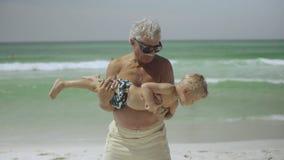 Το Granddad και ο εγγονός του έχουν τη διασκέδαση στην παραλία 4k απόθεμα βίντεο