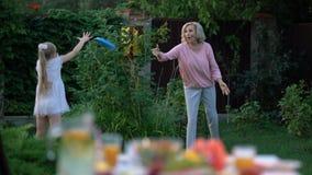 Το Grandma διδάσκει την εγγονή πώς να παίξει ρίχνει και πιάνει το παιχνίδι, ενεργός τρόπος ζωής απόθεμα βίντεο