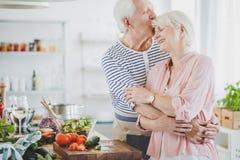 Το Grandpa αγκαλιάζει και φιλά το grandma χαμόγελου στοκ εικόνα με δικαίωμα ελεύθερης χρήσης