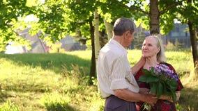 Το Grandpa αγκαλιάζει το grandma του στο υπόβαθρο των δέντρων απόθεμα βίντεο