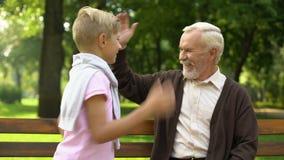 Το Grandpa δίνει υψηλός-πέντε στον εγγονό, τη φιλία με το αγόρι και την ανατροφή του απόθεμα βίντεο