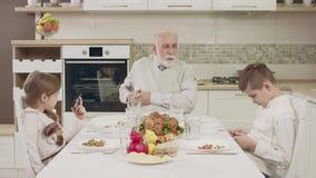 Το Grandpa επικοινωνεί με τα εγγόνια στον πίνακα πριν από ένα οικογενειακό γεύμα απόθεμα βίντεο