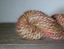 Το Handspun 2 νήμα πτυχών έκανε σε μια περιστρεφόμενη ρόδα από το χονδροειδές μαλλί του Λίνκολν sheep's Στοκ Εικόνες