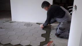 Το Handyman βάζει τα hexagon κεραμίδια στο πάτωμα στο νέο διαμέρισμα κάτω από την κατασκευή απόθεμα βίντεο